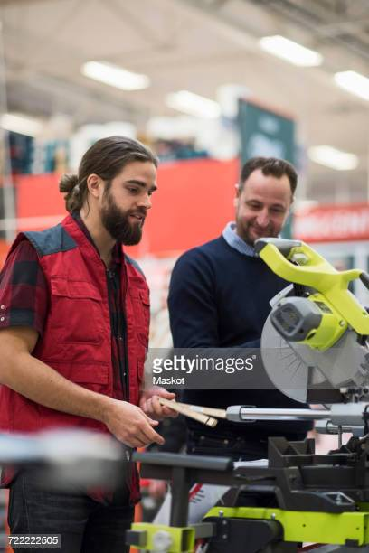 Salesman explaining machinery to male customer in hardware store