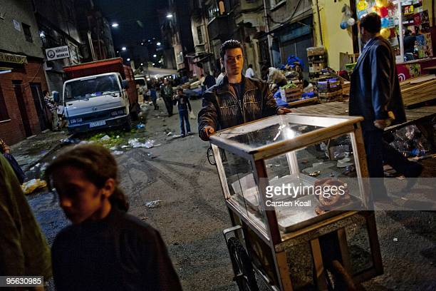 Salesman for pastry pushes his mobile shopthrough the dark streets in the district Tarlabasi on May 14, 2006 in Istanbul, Turkey. Tarlabasõ is a...