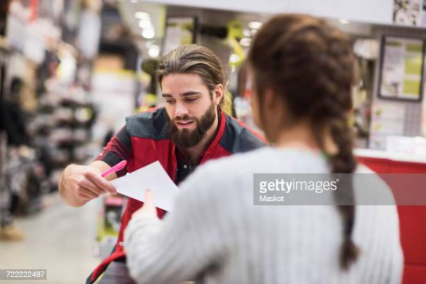 Salesman giving document to female customer in hardware store