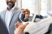Salesman giving new car keys to customer
