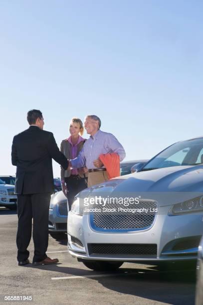 Salesman greeting couple in car dealership lot