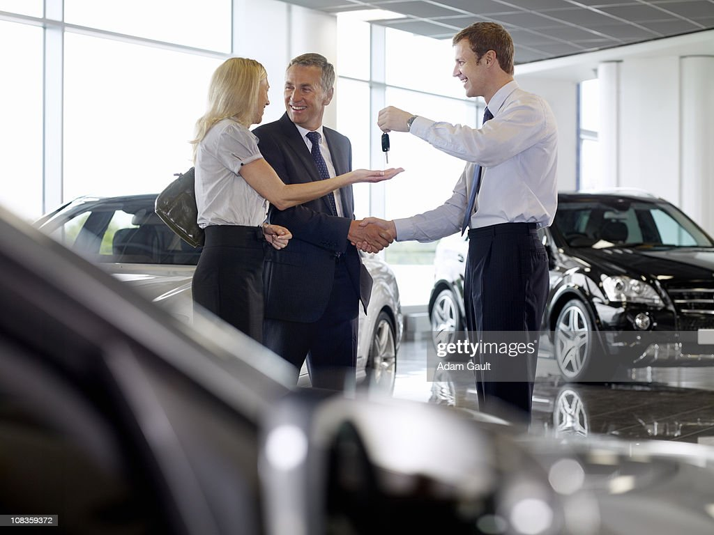 Salesman Handing Couple Keys To New Car In Showroom Stock Photo