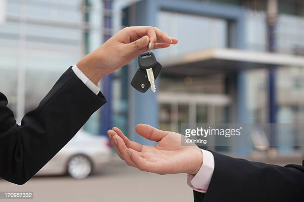 Salesman handing over car keys, close up on hands