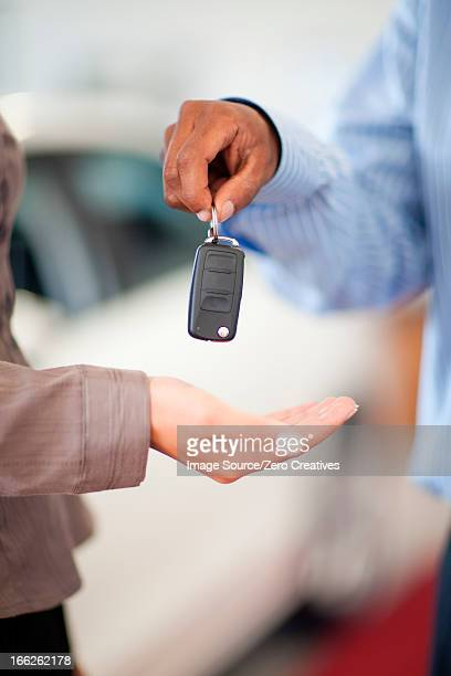 Salesman handing woman new car keys