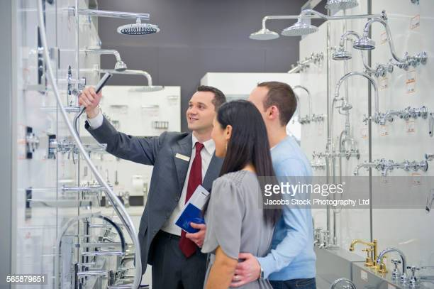 Salesman helping couple shopping for bathroom fixture in store