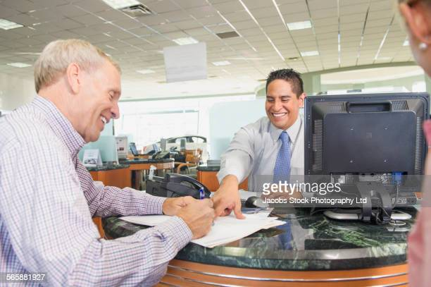 Salesman helping couple sign paperwork in car dealership