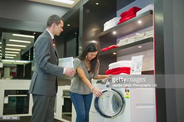 Salesman helping woman shopping for washing machine in store