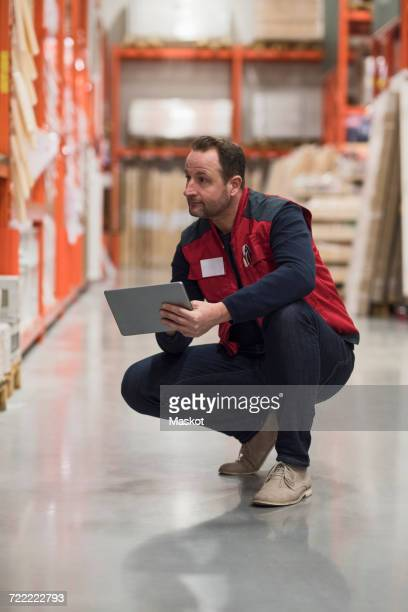 Salesman holding digital tablet while looking at shelf in hardware store