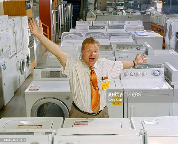 salesman in appliance store with arms outstretched, portrait - short sleeved stock pictures, royalty-free photos & images