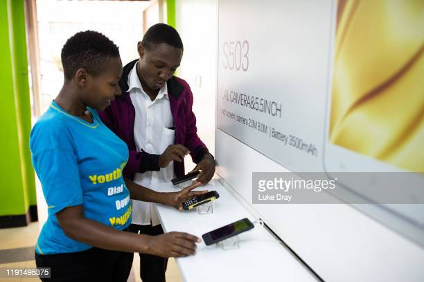 Salesman interacts with a customer on December 02, 2019 in Kampala, Uganda. Uganda's first mobile phone electronics factory has been operating in...