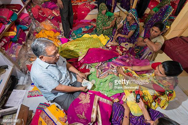 A salesman is promoting colorful material in his shop in a small street of the old walled Pink City
