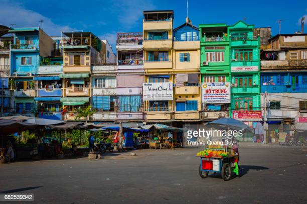 a salesman is pushing a car under the colorful street at an dong market. - ho chi minh city stock pictures, royalty-free photos & images