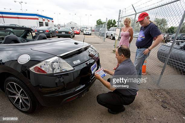 Salesman Ken Roybal places a temporary license on a Mitsubishi Eclipse purchased by Dori and Michael Houx right at Skyline Mitsubishi in Thornton...