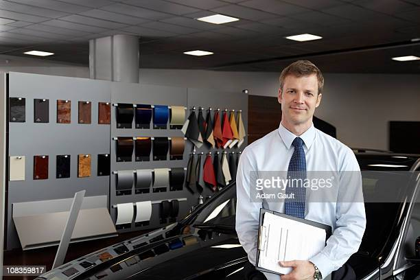 Salesman leaning in new car in showroom