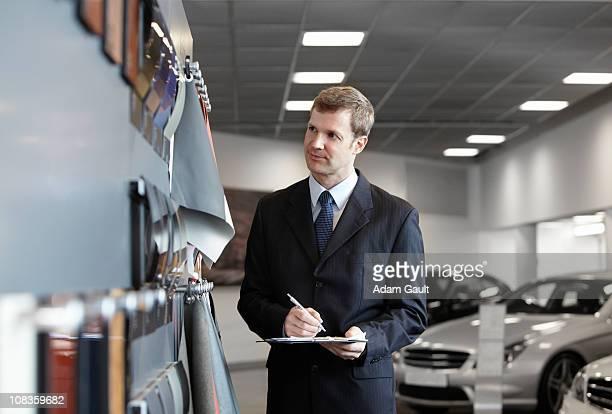 Salesman looking at fabric samples in automobile showroom