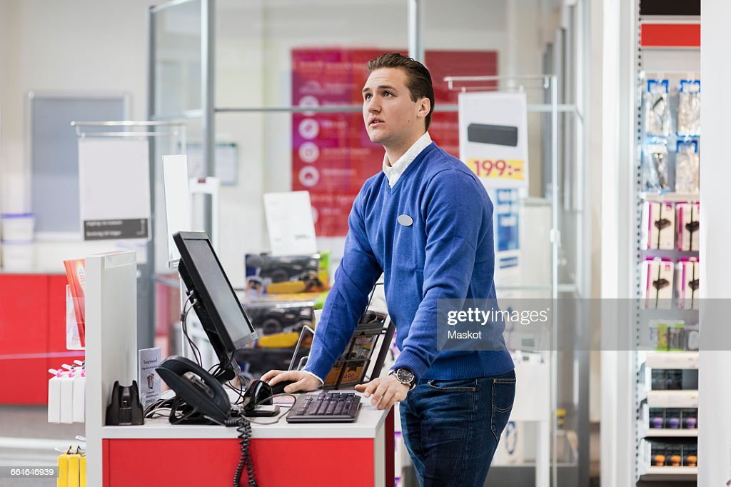 Salesman looking up while standing at counter in store : Stock Photo