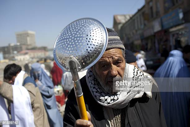 A salesman offers strainers for sale as pedestrians walk through a market area in the old city of Kabul Afghanistan March 4 2009 Kabul has an...
