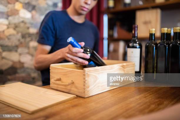 salesman packing a wine bottle in wooden box - wine stock pictures, royalty-free photos & images