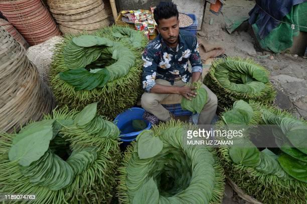 A salesman prepares betel leafs in Kawran Bazar wholesale market in Dhaka on December 17 2019