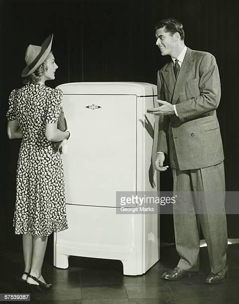 Salesman presenting refrigerator to woman in studio, (B&W)