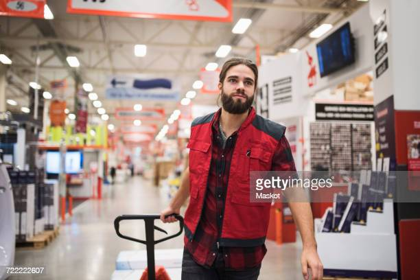 salesman pulling handtruck in hardware store - jacket stock pictures, royalty-free photos & images