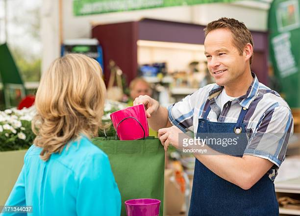 Salesman Putting Product In Shopping Bag