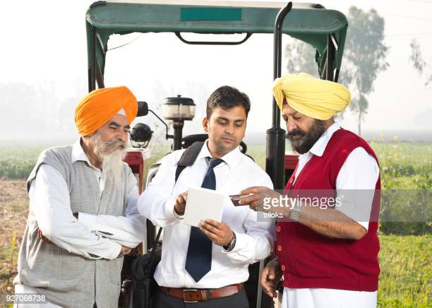 Salesman receiving payment for new tractor using digital tablet and credit card