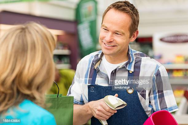 Salesman Scanning Merchandise For Checkout