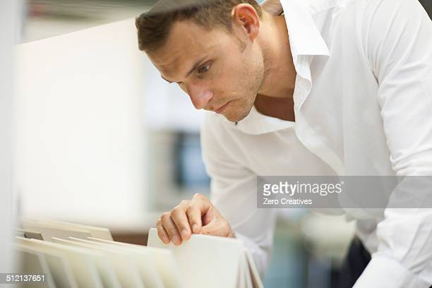 Salesman searching in filing cabinet in kitchen showroom