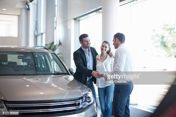 Salesman shaking hands with mid adult couple in car dealership