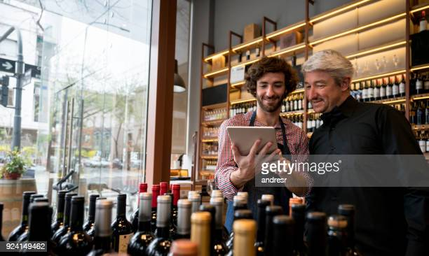 Salesman showing a wine app to a customer at a winery both looking very happy and smiling
