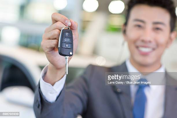 Salesman showing car key