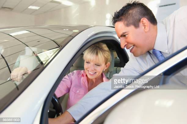 salesman showing car to woman in dealership - sells arizona stock pictures, royalty-free photos & images