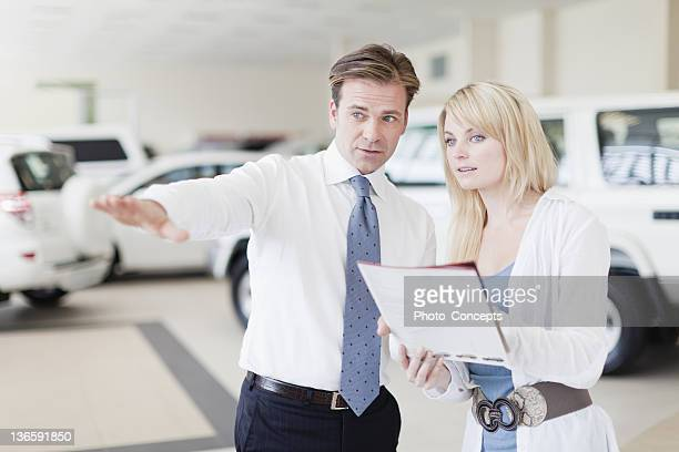 Salesman showing cars to customer