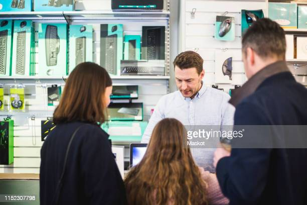 Salesman showing computer equipment to customers in electronics store