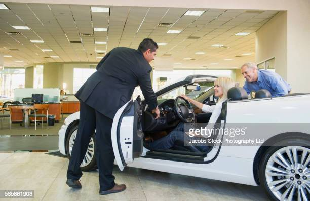 salesman showing convertible to couple in car dealership - sells arizona stock pictures, royalty-free photos & images