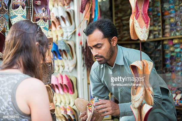 salesman showing shoes to woman shopping at souk, dubai, uae - bazaar stockfoto's en -beelden