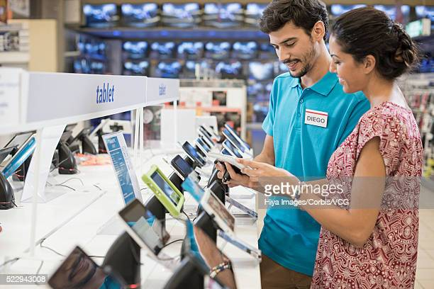 salesman showing to woman digital tablet - electronics store stock photos and pictures