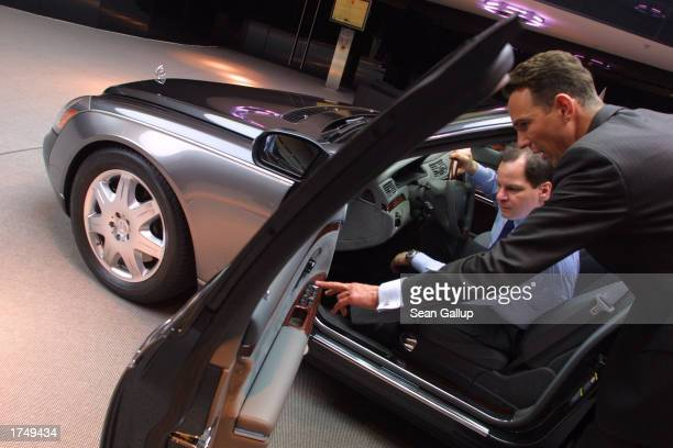 A salesman shows a potential customer details of a Maybach 57 limousine which retails for EUR 359 about $390 at a Maybach dealership January 28 2003...