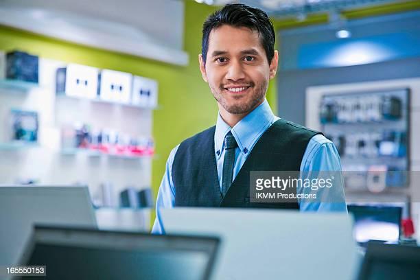 salesman smiling in store - electronics store stockfoto's en -beelden