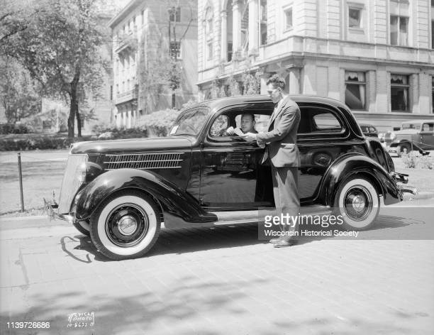 Salesman standing beside new Ford car parked beside the UW YMCA 740 Langdon Street with Harry Stuhldreher University of WisconsinMadison football...