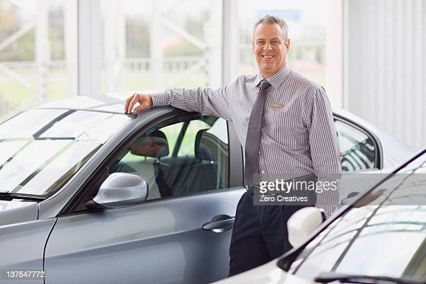 Salesman standing by car in showroom