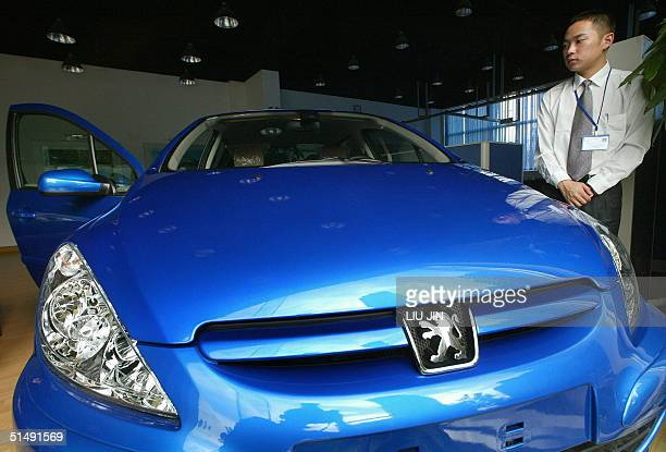 A salesman stands beside a newly Peugeot 307 made by DongfengPeugeot company at a showroom in Shanghai 18 October 2004 PSA Peugeot Citroen China's...