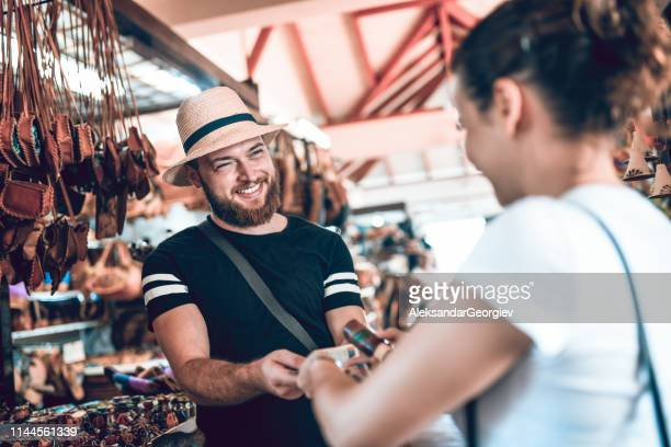 salesman successfully selling leather bag to female tourist - market vendor stock pictures, royalty-free photos & images
