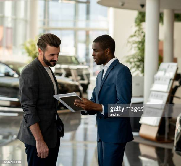 salesman talking to a happy man at a car dealership - test drive stock pictures, royalty-free photos & images
