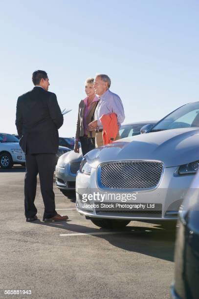 salesman talking to couple in car dealership lot - sells arizona stock pictures, royalty-free photos & images