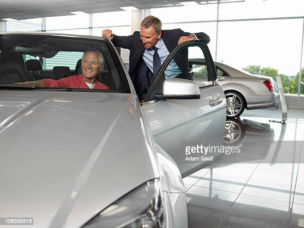 Salesman talking to man in new car in showroom