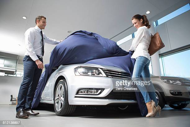 Salesman uncovering new car to female customer in car dealership