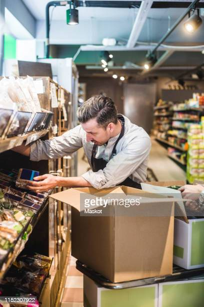 salesman unloading cardboard box while arranging packets on shelf in store - unloading stock pictures, royalty-free photos & images