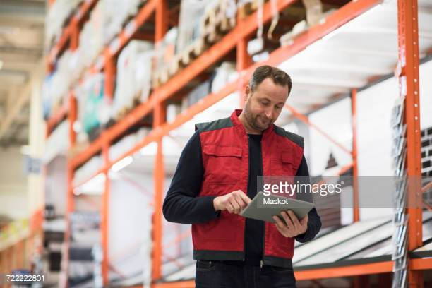 salesman using digital tablet while standing by shelf in hardware store - icon set stock photos and pictures